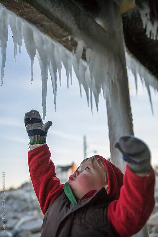 Child Reaching for Icicle by Raymond Forbes LLC for Stocksy United