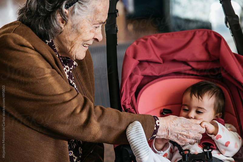 Senior woman playing with a baby - Family moment of great grandmother and great granddaughter by Alejandro Moreno de Carlos for Stocksy United