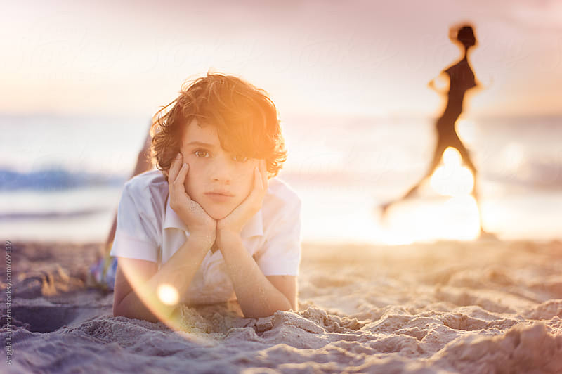 Boy lying on the beach at sunset by Angela Lumsden for Stocksy United