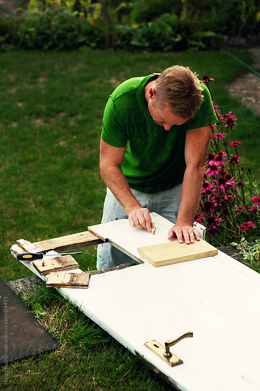 A man doing DIY in his garden by Helen Rushbrook for Stocksy United