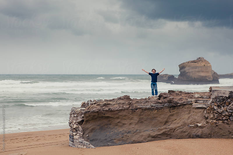 Boy standing on a big rock on the beach during a storm by Cindy Prins for Stocksy United