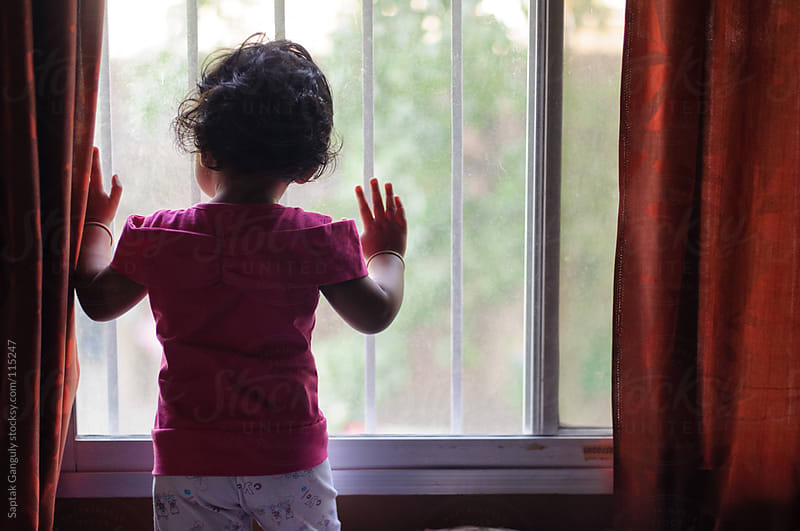 Baby girl standing by the window,rear view by Saptak Ganguly for Stocksy United
