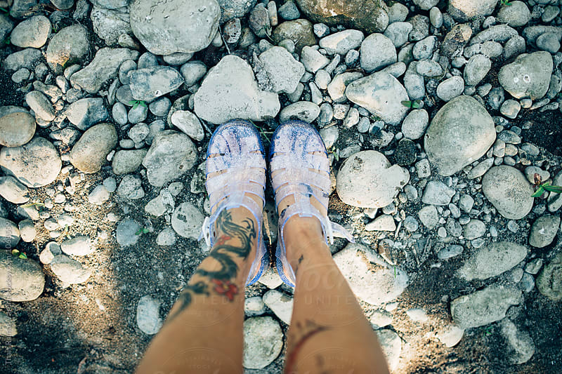 woman feet standing on stones by Thais Ramos Varela for Stocksy United