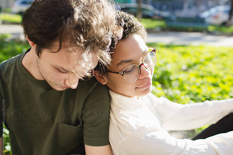 Tender mixed-race couple relaxing outdoors by michela ravasio for Stocksy United