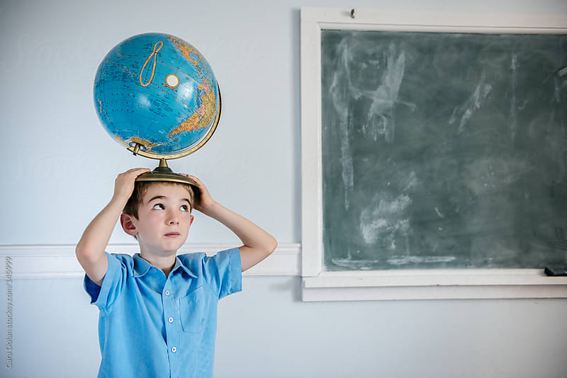 Student in a classroom holds a school globe on top of his head by Cara Dolan for Stocksy United