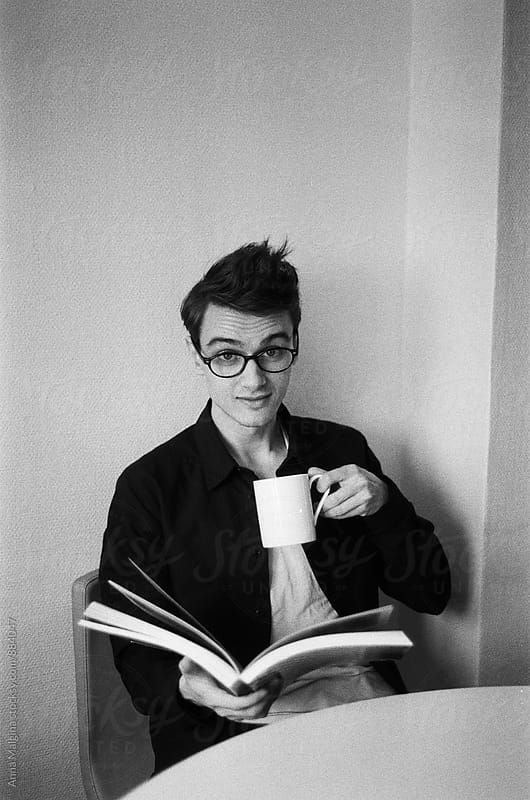 A black and white film portrait of a young beautiful man with a book and a cup by Anna Malgina for Stocksy United