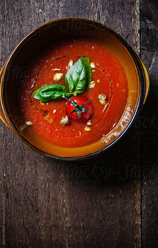 Bowl of homemade tomato soup on table. by Darren Muir for Stocksy United