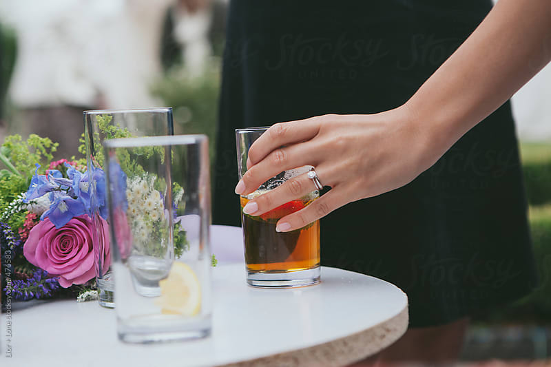 Female hand with wedding diamond ring at reception by Lior + Lone for Stocksy United
