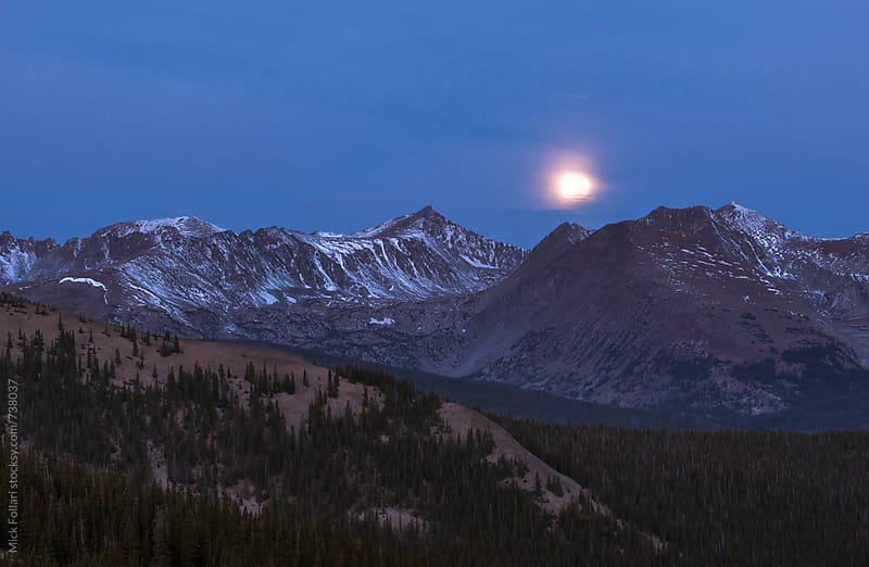 Blood moon setting in the mountains by Mick Follari for Stocksy United
