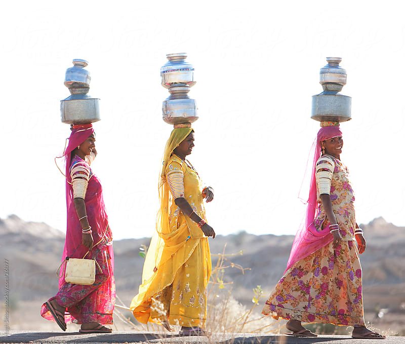 Indian women carrying water jugs to their homes. Thar Desert. by Hugh Sitton for Stocksy United