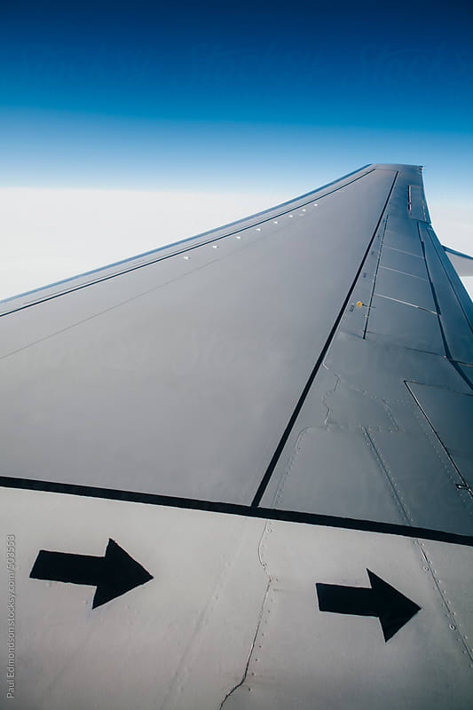 Airplane wing and sky from above by Paul Edmondson for Stocksy United