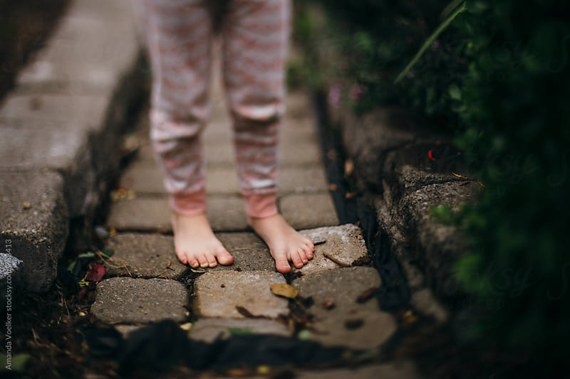 Bare feet and pajama bottoms on a cobblestone garden path by Amanda Voelker for Stocksy United