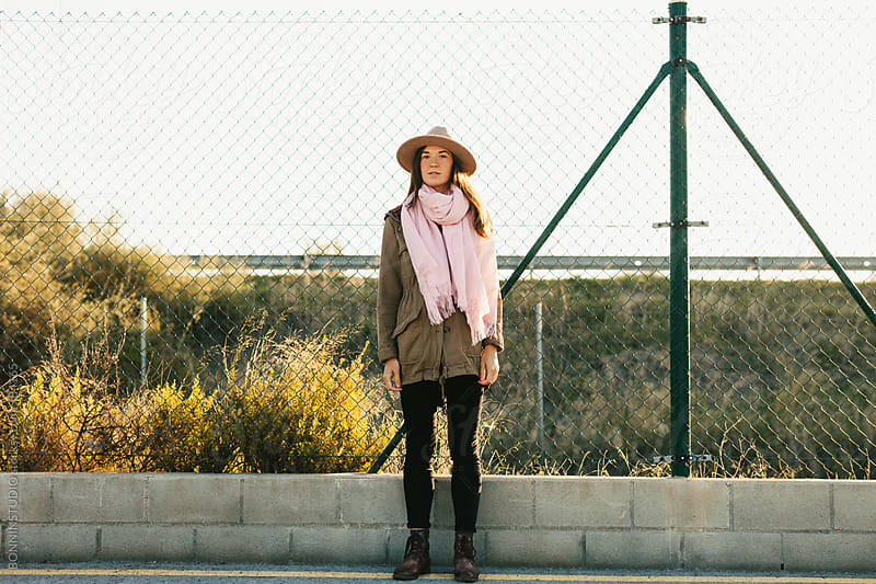 Young hipster woman standing by a fence on a sunny winter day. by BONNINSTUDIO for Stocksy United