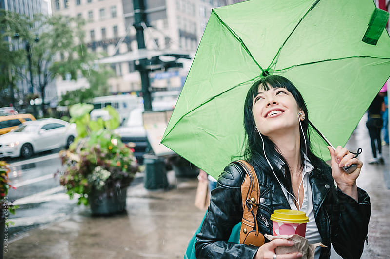 Woman walking under the rain in New York City by GIC for Stocksy United