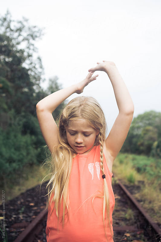 girl playing with glitter on train tracks  by Tahl Rinsky for Stocksy United