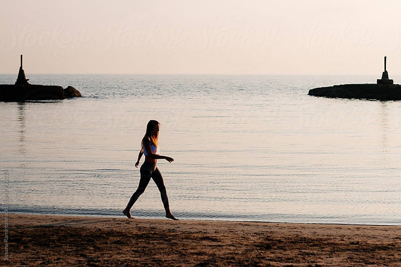 Young woman walking of the beach at sunset by Susana Ramírez for Stocksy United