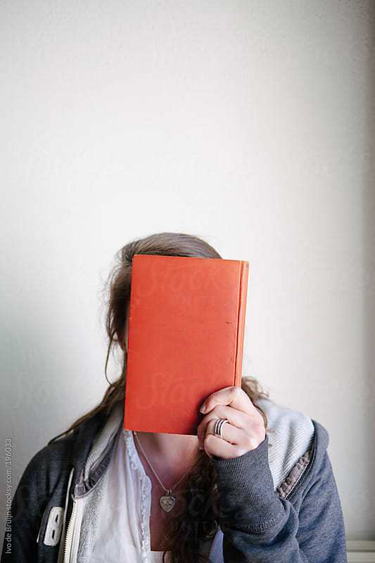 Girl holding a book in front of her face, being fed up with studying by Ivo de Bruijn for Stocksy United