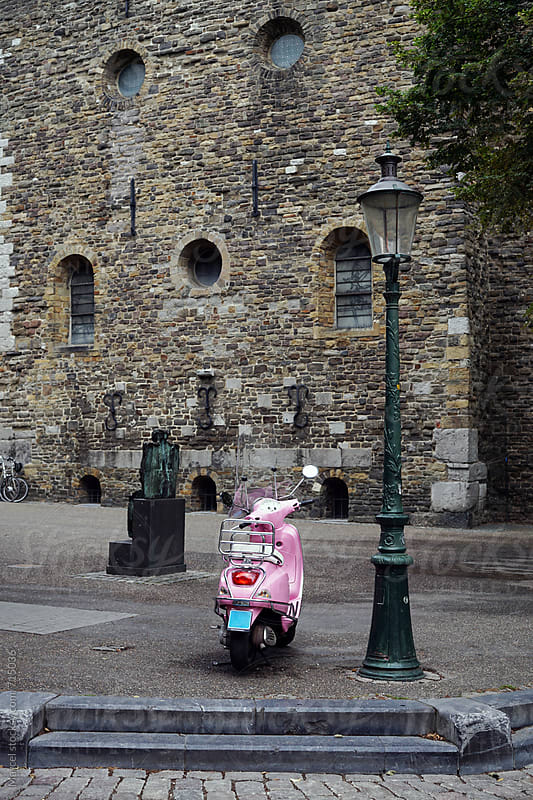 Pink scooter in front of an old church by Marcel for Stocksy United