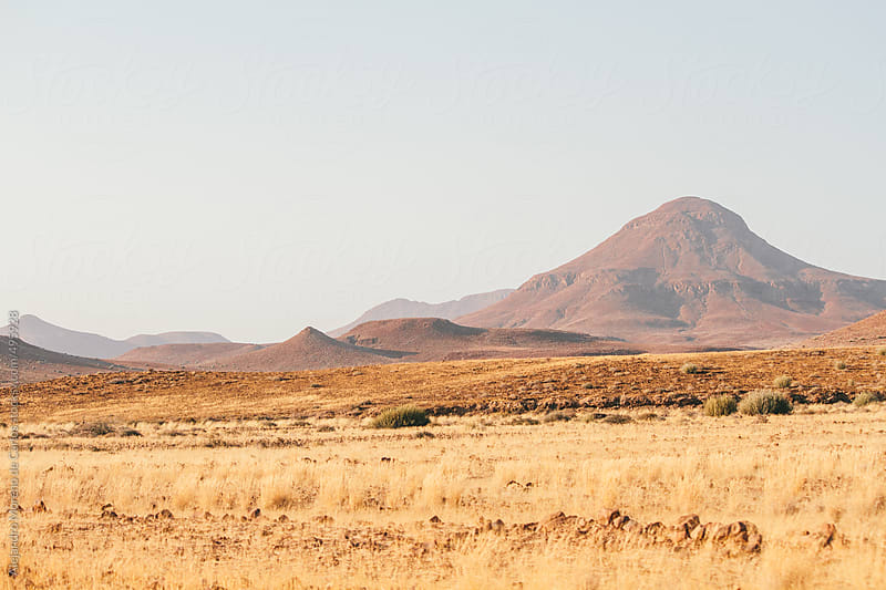 Mountain on arid desertic landscape, Namibia by Alejandro Moreno de Carlos for Stocksy United