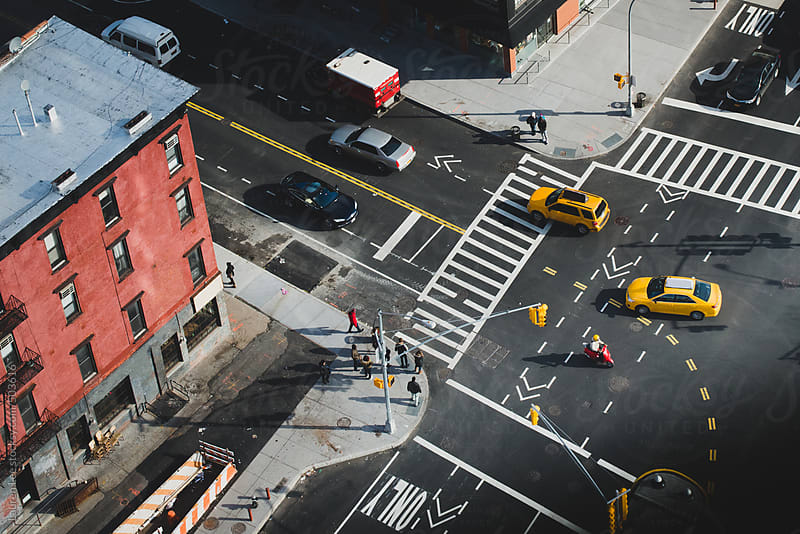 Taxi cabs and city dwellers on a busy city block by Lauren Naefe for Stocksy United