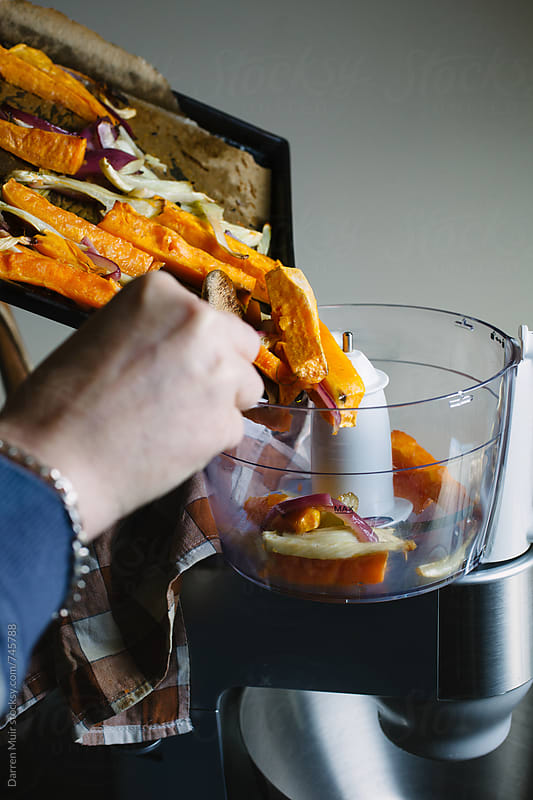 Woman's hands pushing roasted vegetables from an oven tray into a blender. by Darren Muir for Stocksy United