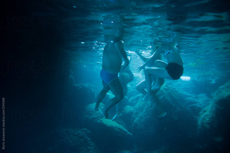 Group of friends swimming in the cave, underwater shot by Boris Jovanovic for Stocksy United