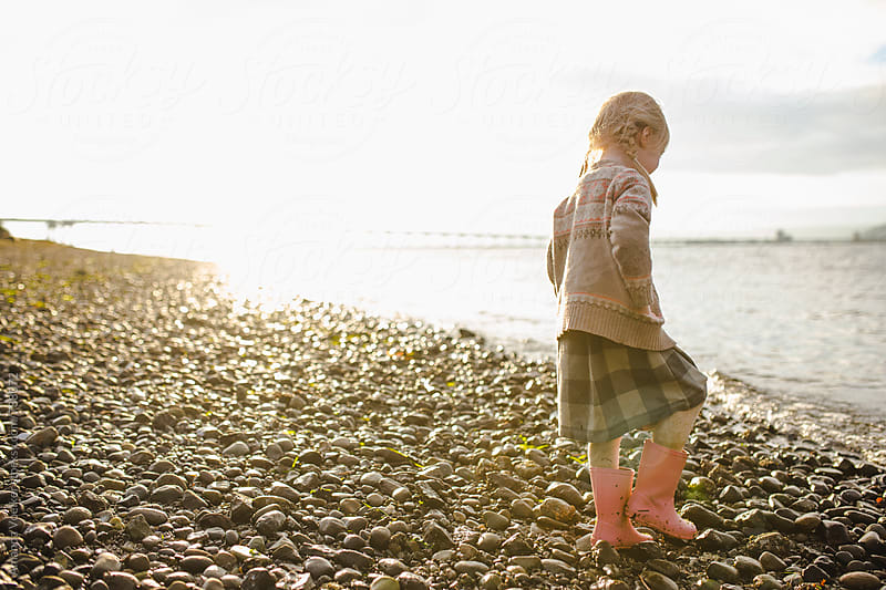 Side view of a little girl standing in the sunset along the rocky shore by Amanda Voelker for Stocksy United