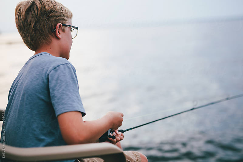 boy reeling in a fish by Kelly Knox for Stocksy United