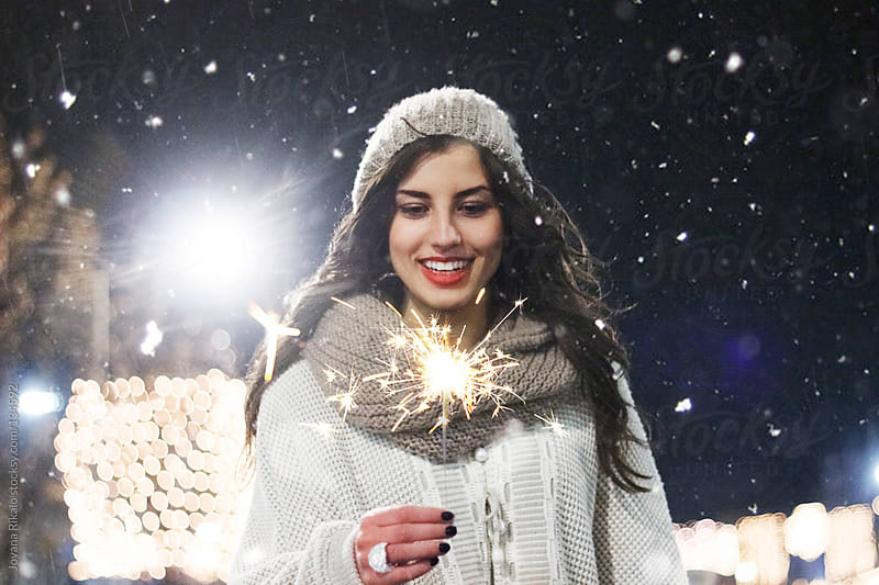 Pretty girl holding sparkler in her hand and smiling by Jovana Rikalo for Stocksy United