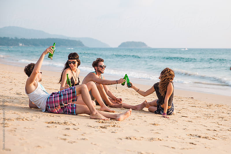Friends enjoying cold drinks at the beach by Jovo Jovanovic for Stocksy United