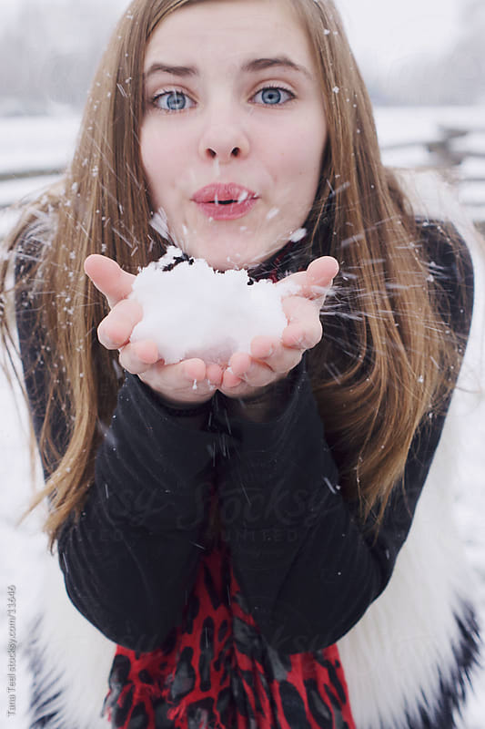 A young girl blowing snow our of her hands.  by Tana Teel for Stocksy United