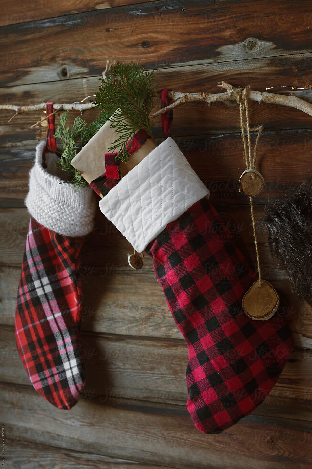 Christmas stockings hung on rustic wall by tana teel for stocksy united