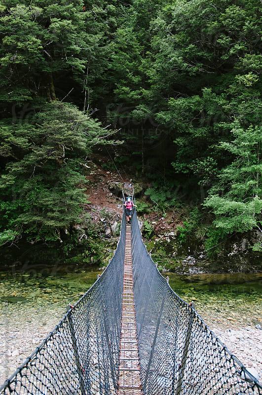 Woman crossing swing bridge, Kahurangi National Park, New Zealand. by Thomas Pickard for Stocksy United