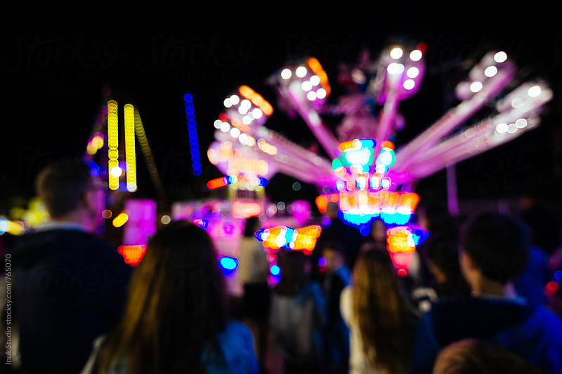 Blurred scene of people in a fair at night with colourful lights and attractions by Inuk Studio for Stocksy United