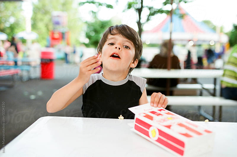 boy eating popcorn at amusement park by Maria Manco for Stocksy United