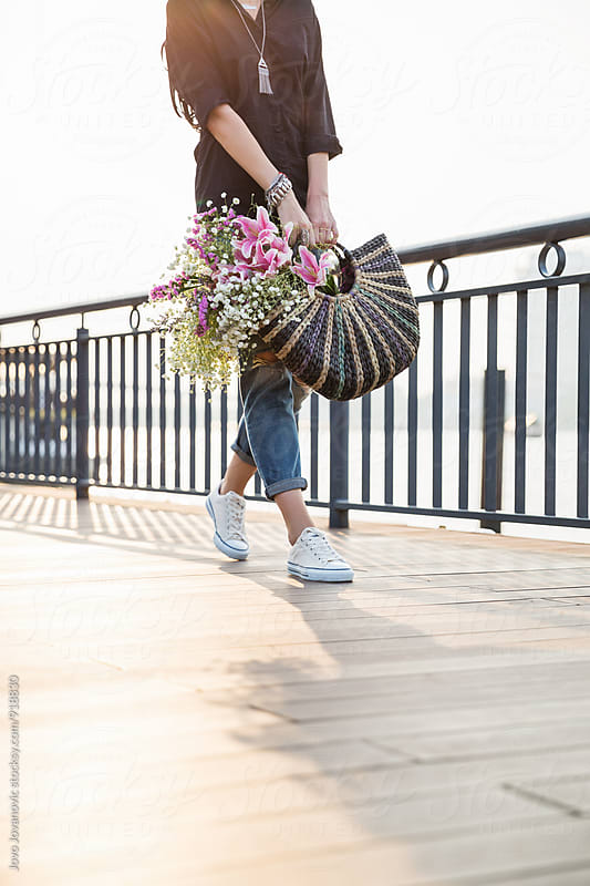 Young woman in the city holding a bouquet of flowers by Jovo Jovanovic for Stocksy United