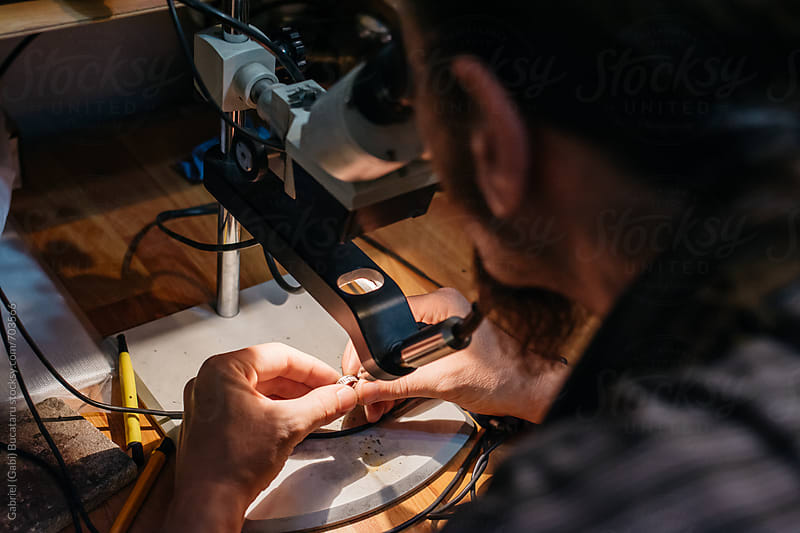 Jeweler repairing a ring with a welding machine by Gabriel (Gabi) Bucataru for Stocksy United