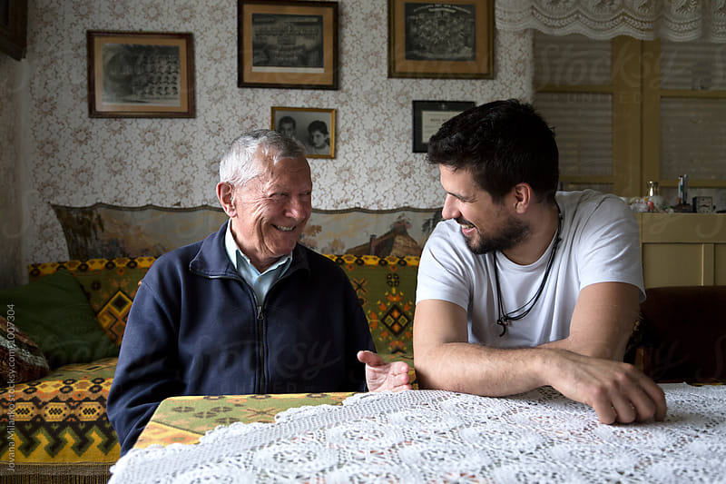 Grandfather and his grandson talking and laughing while spending time together by Jovana Milanko for Stocksy United