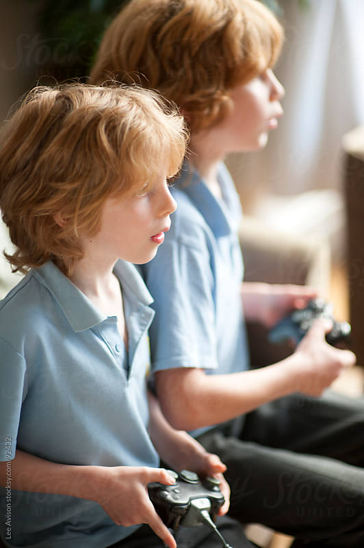 two brothers playing computer games together by Lee Avison for Stocksy United