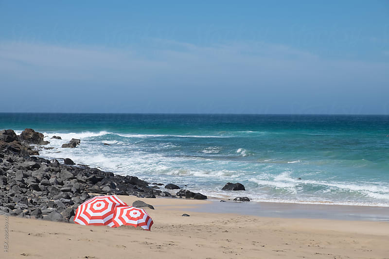 Striped Red and White Beach Umbrella Close to the Beach by HEX. for Stocksy United