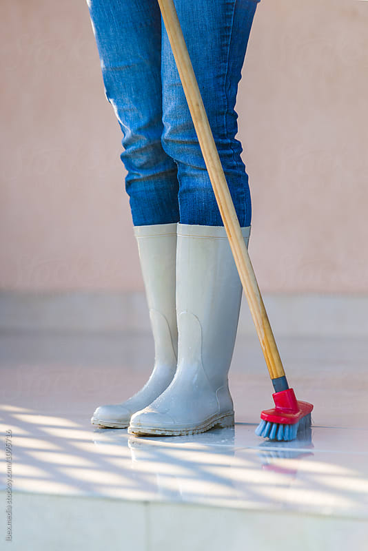 Feet in rubber boots of a woman washing the porch by RG&B Images for Stocksy United