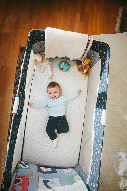 Happy baby boy in a crib by Ivan Bastien for Stocksy United