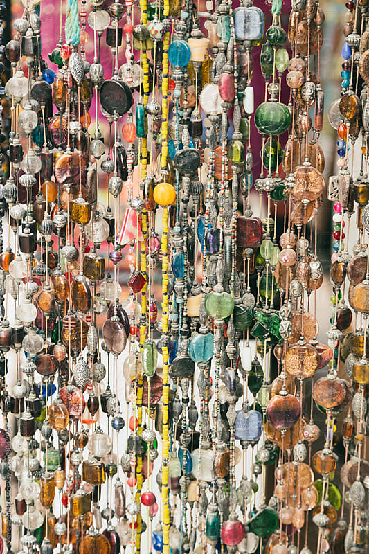 Glass beaded necklaces hanging at a market stall in Morocco by Maresa Smith for Stocksy United