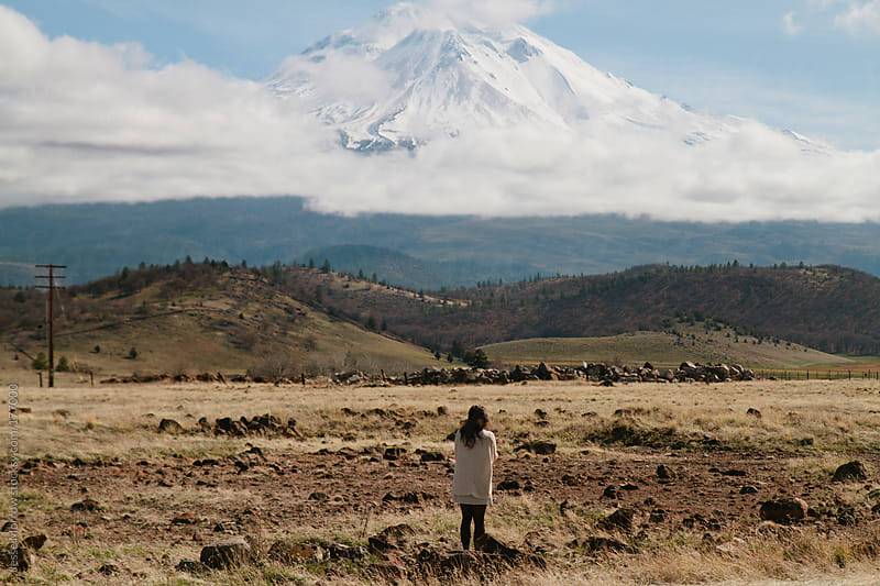 young woman standing in front of mt. shasta by Jesse Morrow for Stocksy United