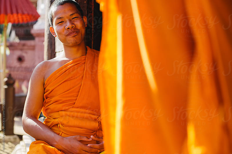 Portrait of a young Buddhist monk smiling  by michela ravasio for Stocksy United