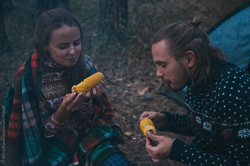Couple eating corn in the forest by Danil Nevsky for Stocksy United