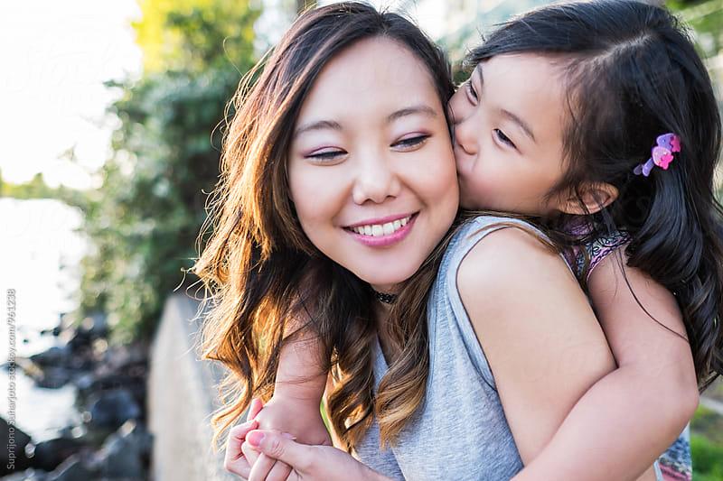 Happy Asian girl kissing her mother by Suprijono Suharjoto for Stocksy United