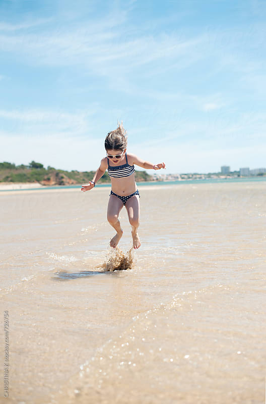 Little girl jumping in the sea by CHRISTINA K for Stocksy United