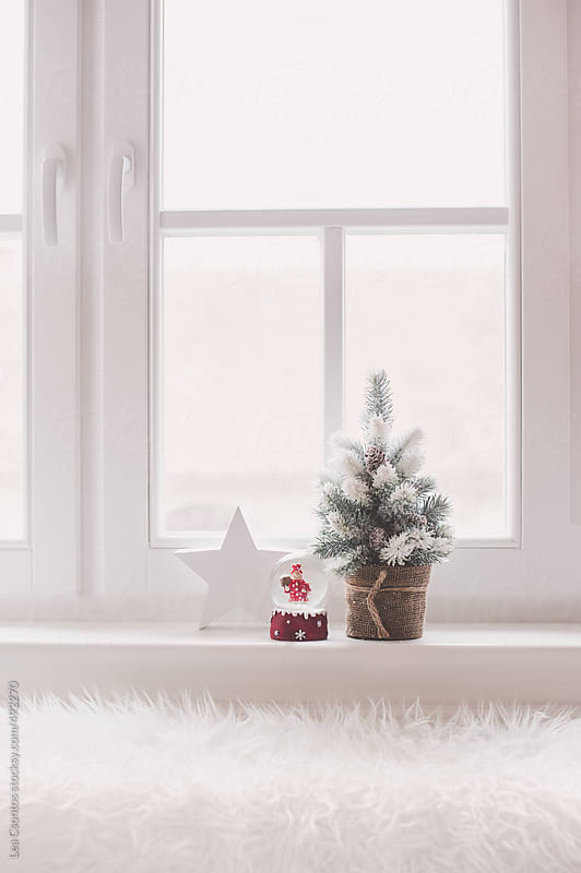 Small snow covered christmas tree with a white wooden star and a snowglobe on a window sill by Lea Csontos for Stocksy United