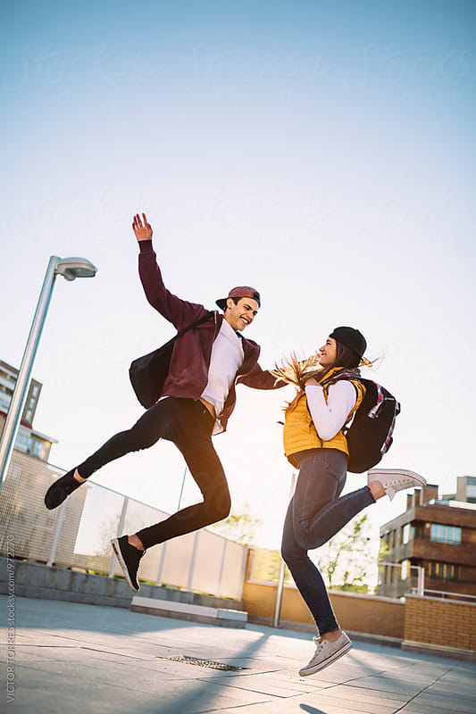 Cheerful Teenager Couple Jumping in the Air by VICTOR TORRES for Stocksy United